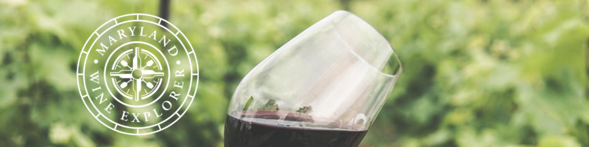 Maryland Wine Explorer banner, red wine glass tilted over vineyard in background