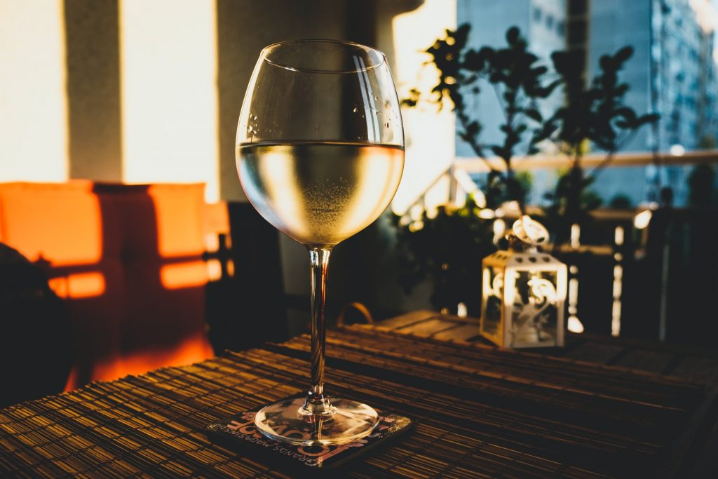 White wine glass sitting in sunny window.